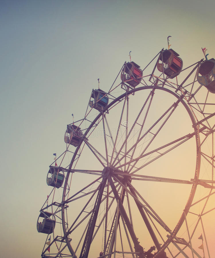 Carnival Ferris Wheel in Sunset Sky at Night. A Ferris wheel is spinning at a carnival at sunset for an artistic activity or summer memory concept stock photography