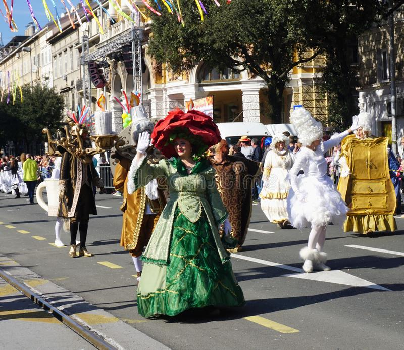 Carnival group of masked people in the costume from Beauty and the beast film greetings on the parade stock photography