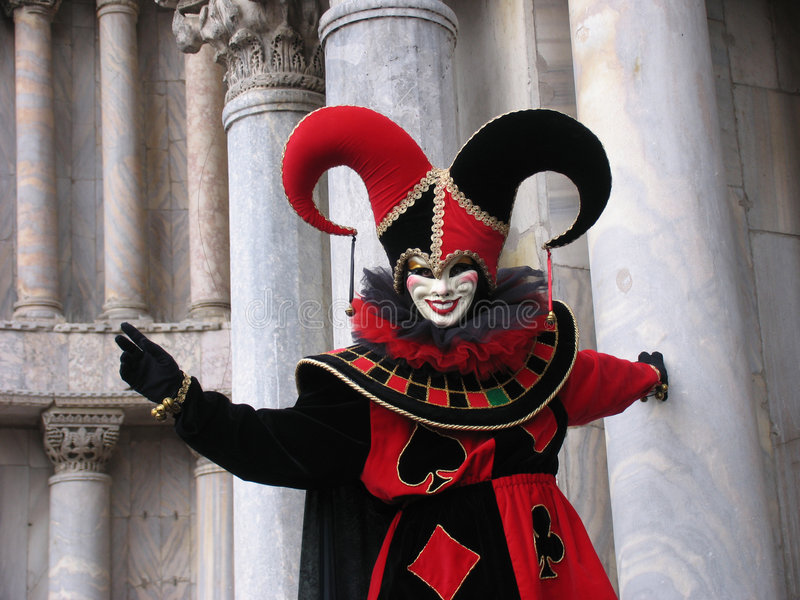 Carnival: joker mask in front of pillars. Carnival of Venice, Italy: Person wearing grining mask and joker costume in the colors red and black. A roulette wheel royalty free stock image