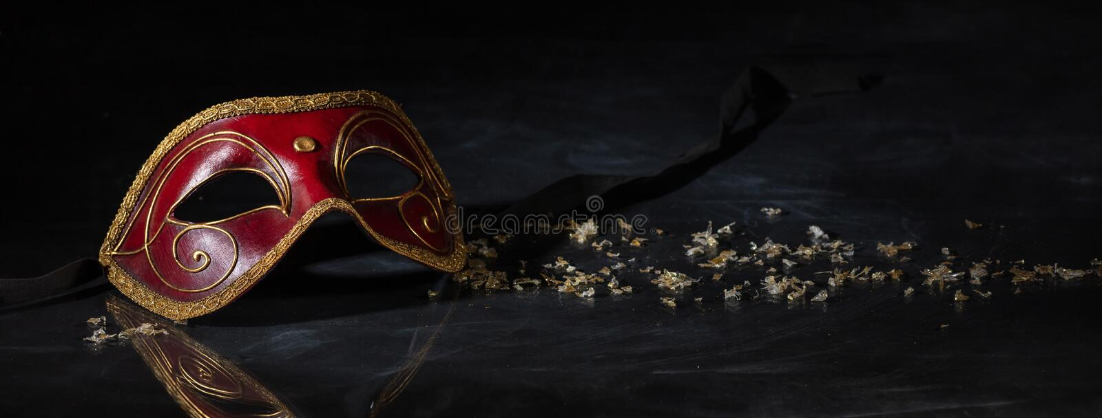 Carnival mask on black background, reflections, banner. Carnival time. Venetian mask red and gold color on black background, reflections, banner stock photos