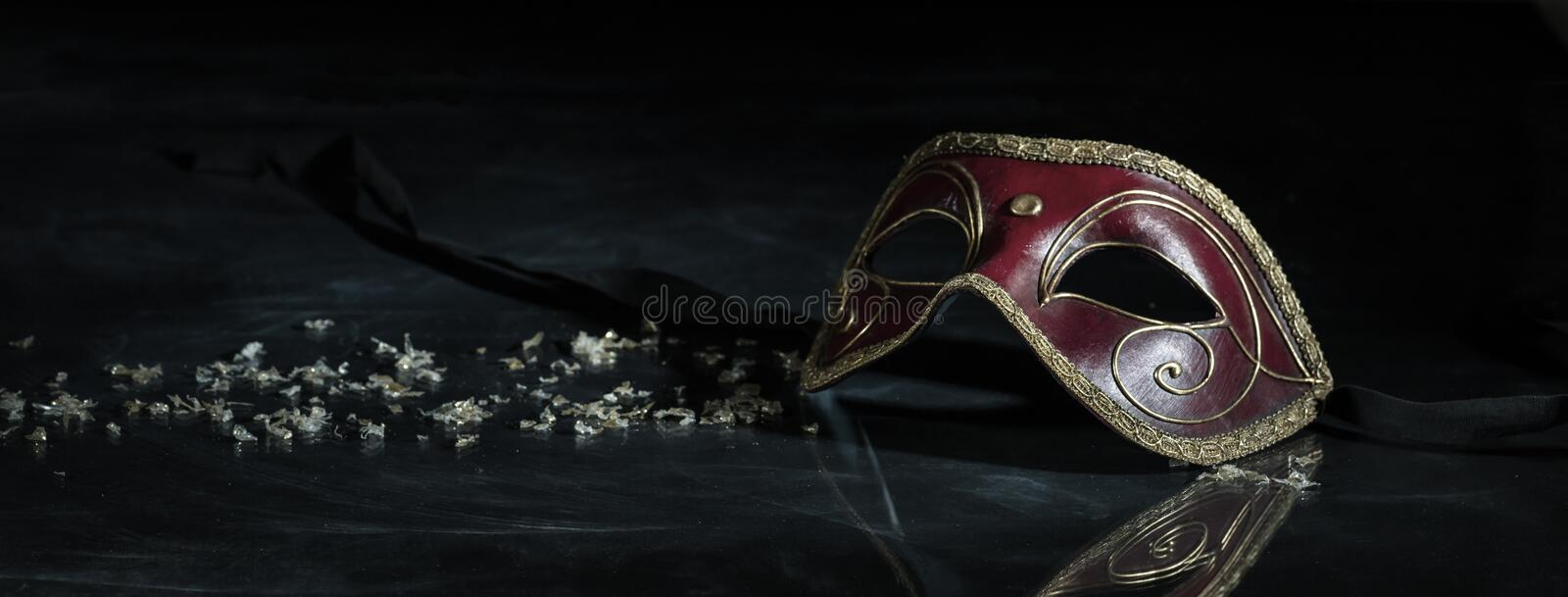 Carnival mask on black background, reflections, banner. Carnival time. Venetian mask red and gold color on black background, reflections, banner stock image