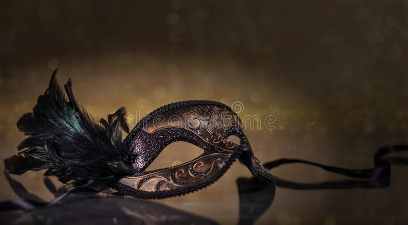 Carnival mask with feathers on dark golden background. Carnival time. Venetian mask with feathers on dark golden background, reflections, copy space stock photo