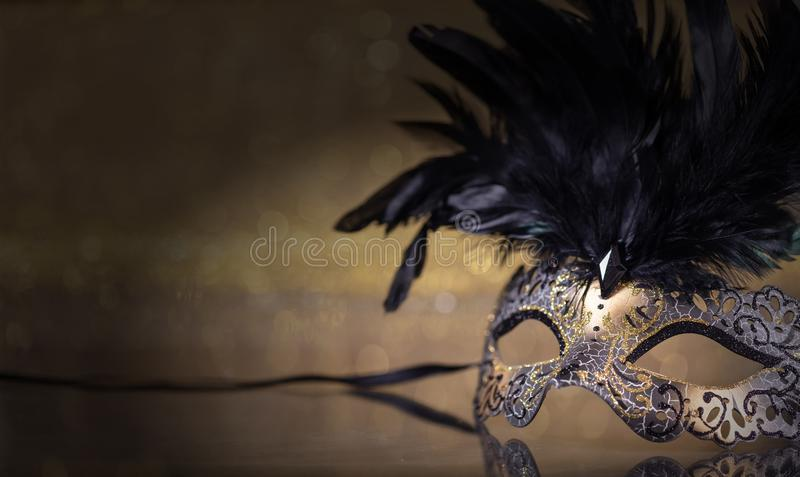Carnival mask with feathers on dark golden background. Carnival time. Venetian mask with feathers on dark golden background, reflections, copy space stock image