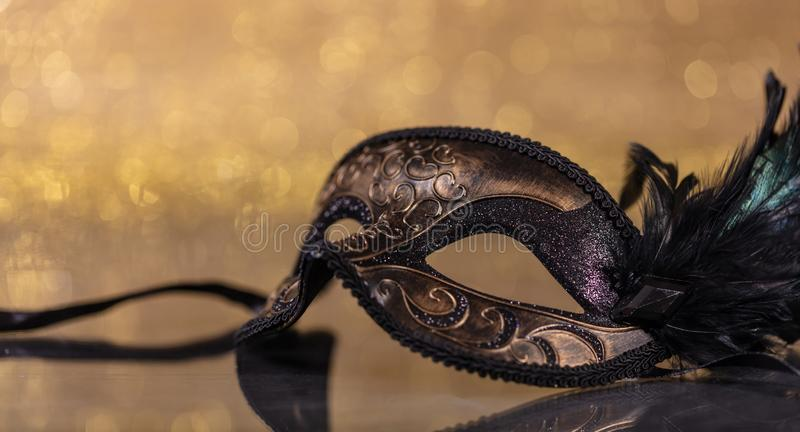 Carnival mask with feathers on golden bokeh background. Carnival time. Venetian mask with feathers on golden bokeh background, reflections, copy space royalty free stock photo