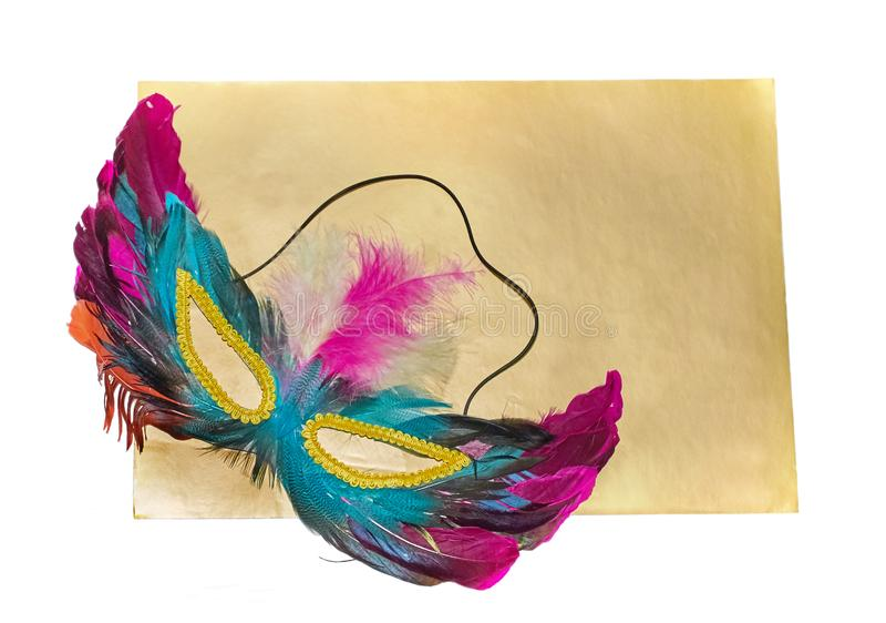 Carnival mask with feathers lies on gold background isolated stock photography