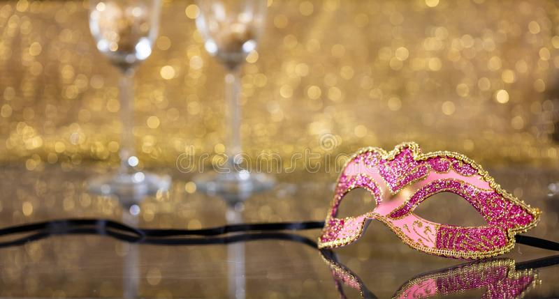 Carnival mask on golden bokeh background, copy space. Carnival party. Venetian mask and champagne glasses on golden bokeh background, reflections, copy space stock images