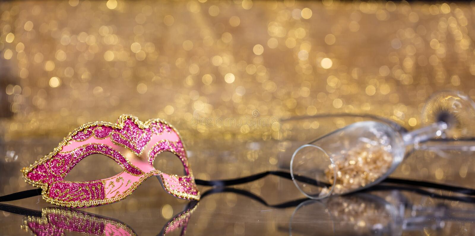 Carnival mask on golden bokeh background, copy space. Carnival party. Venetian mask and champagne glasses on golden bokeh background, reflections, copy space stock photos