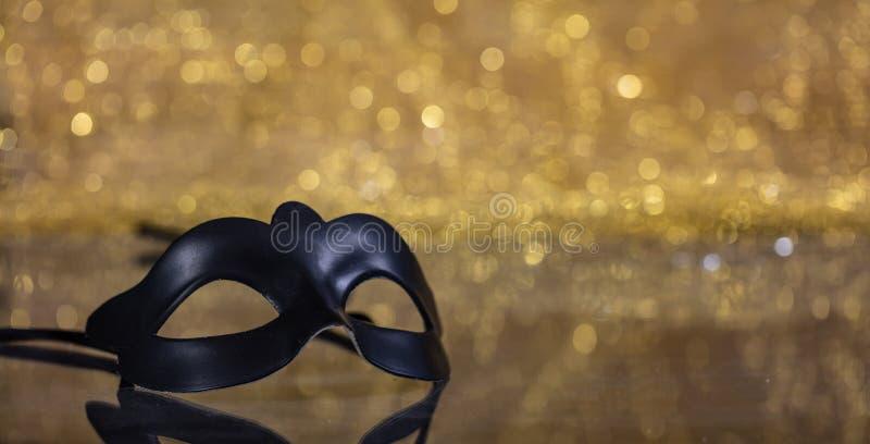 Carnival mask on golden bokeh background, copy space. Carnival time. Venetian black mask on golden bokeh background, reflections, copy space stock photos