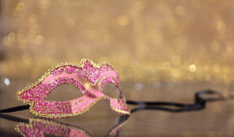 Carnival mask on golden bokeh background, copy space. Carnival time. Venetian pink mask on golden bokeh background, reflections, copy space stock photos