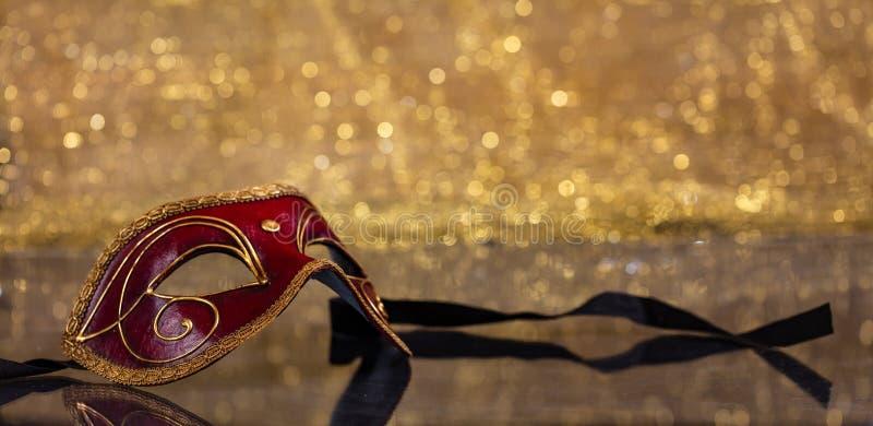 Carnival mask on golden bokeh background, copy space. Carnival time. Venetian red mask on golden bokeh background, reflections, copy space stock photos