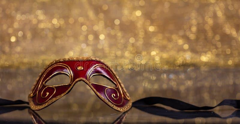 Carnival mask on golden bokeh background, copy space. Carnival time. Venetian red mask on golden bokeh background, reflections, copy space stock image