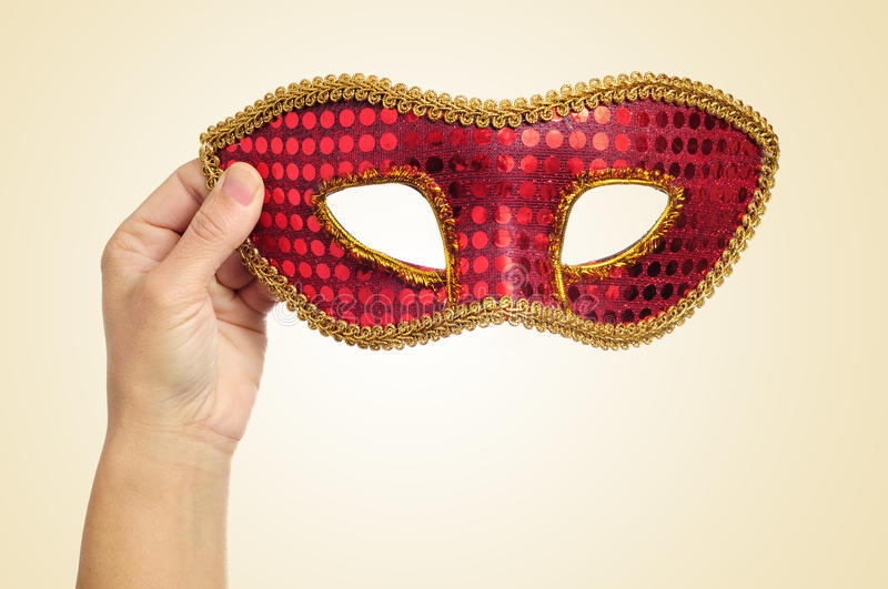 Carnival mask in the hand of a young woman royalty free stock image