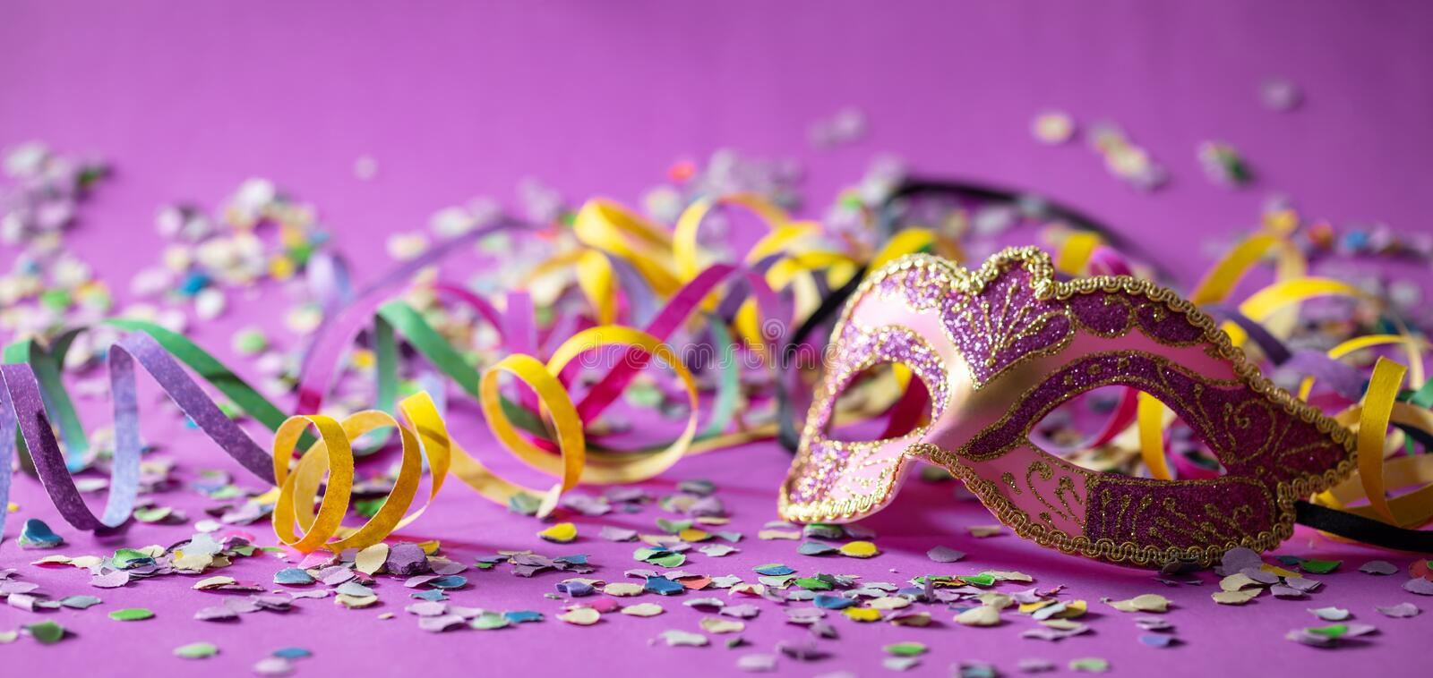 Carnival mask, streamers and confetti on purple background royalty free stock photos