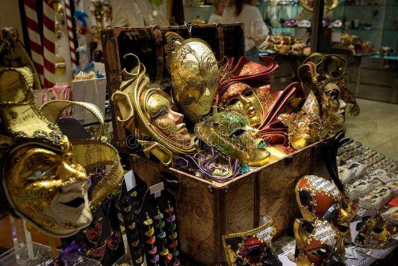 Carnival masks in store window, Venice, Italy. Famous Venetian festival is an annual costume celebration attracts many tourists. Beautiful gold masks and stock photo