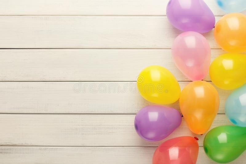 Colorful balloons on white rustic wood, birthday background, top view royalty free stock photo