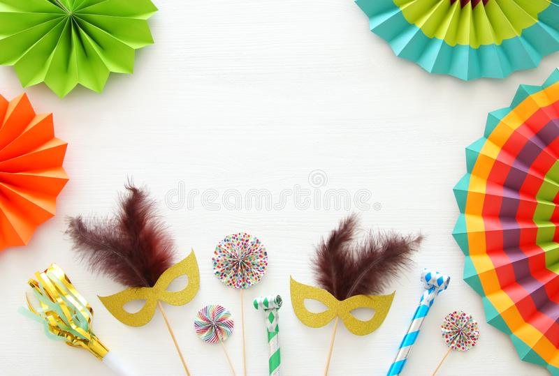 carnival party celebration concept with gold and silver masks over white wooden background and colorful fans. Top view. royalty free stock photo