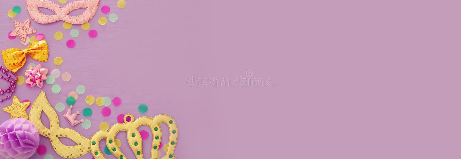 Carnival party celebration concept with mask and colorful party accessories over purple wooden background. Top view. Flat lay. Carnival party celebration stock photos