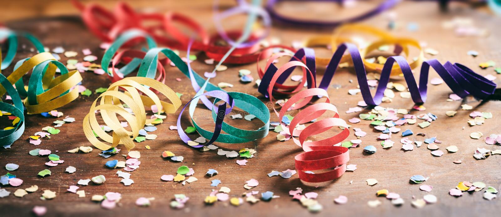 Colorful confetti and serpentines on wooden background. Carnival party. Colorful confetti and serpentines on wooden background royalty free stock photo