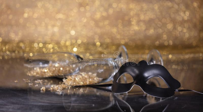 Carnival mask on golden bokeh background, copy space. Carnival party. Venetian black mask and champagne glasses on golden bokeh background, reflections, copy stock photo