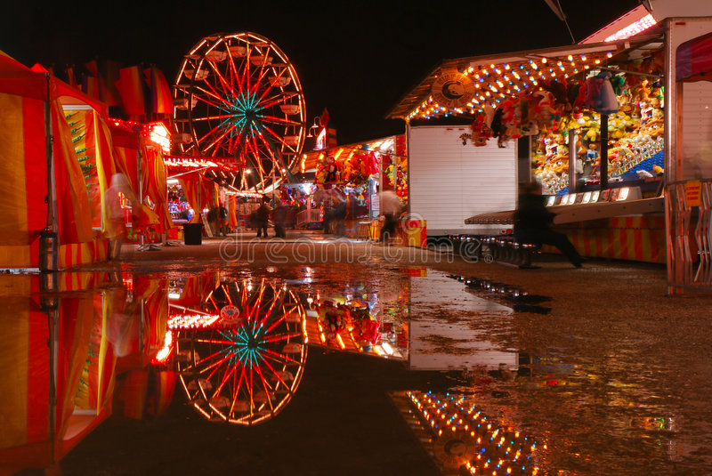 Carnival Reflections. Carnival lights are reflecting in pools of water royalty free stock photography
