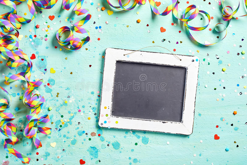 Carnival streamer border with chalkboard. Carnival or party streamer border with a blank vintage slate chalkboard and scattered confetti on a light blue wood stock photography