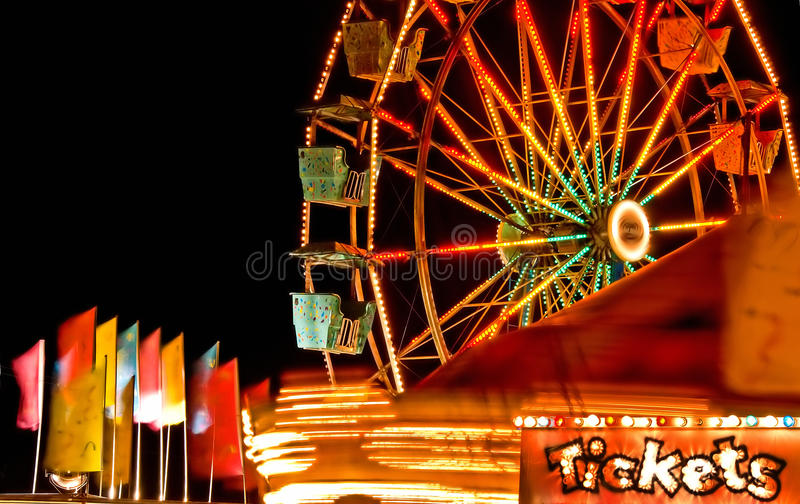 Carnival ticket. A lit ticket sign with a background of moving rides, Ferris wheel, wind-blowing colorful flags at a carnival at night stock photography
