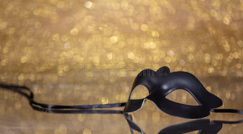 Carnival mask on golden bokeh background, copy space. Carnival time. Venetian black mask on golden bokeh background, reflections, copy space stock image