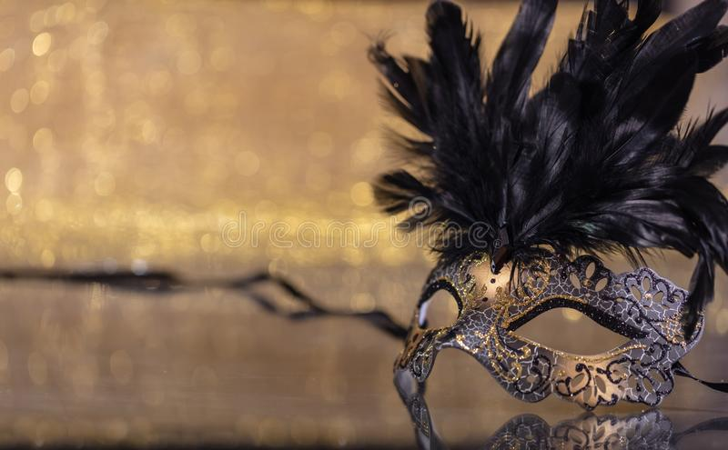 Carnival mask with feathers on golden bokeh background. Carnival time. Venetian mask with feathers on golden bokeh background, reflections, copy space royalty free stock images
