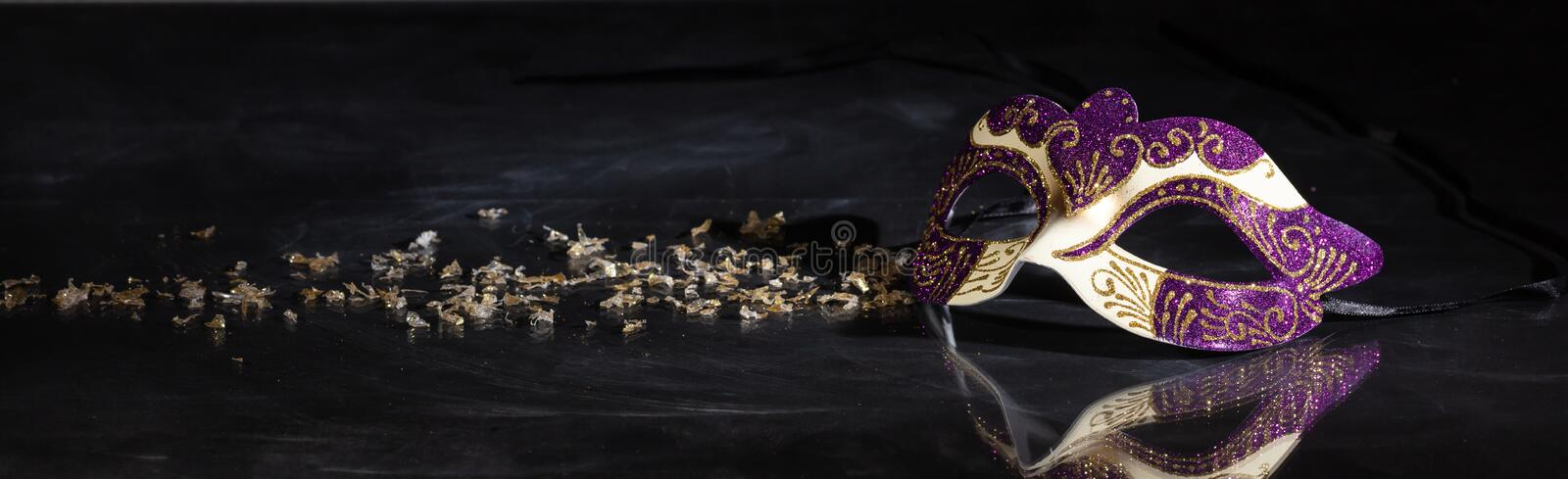 Carnival mask on black background, reflections, banner. Carnival time. Venetian mask purple and gold color on black background, reflections, banner royalty free stock images