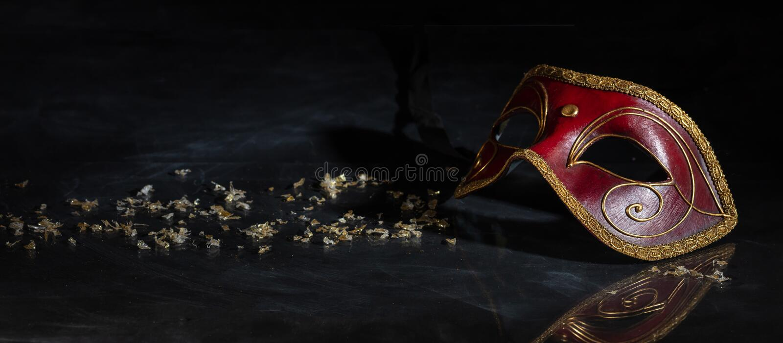Carnival mask on black background, reflections, banner. Carnival time. Venetian mask red and gold color on black background, reflections, banner royalty free stock photos