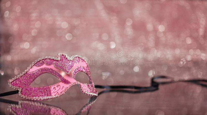 Carnival mask on pink bokeh background, copy space royalty free stock photography
