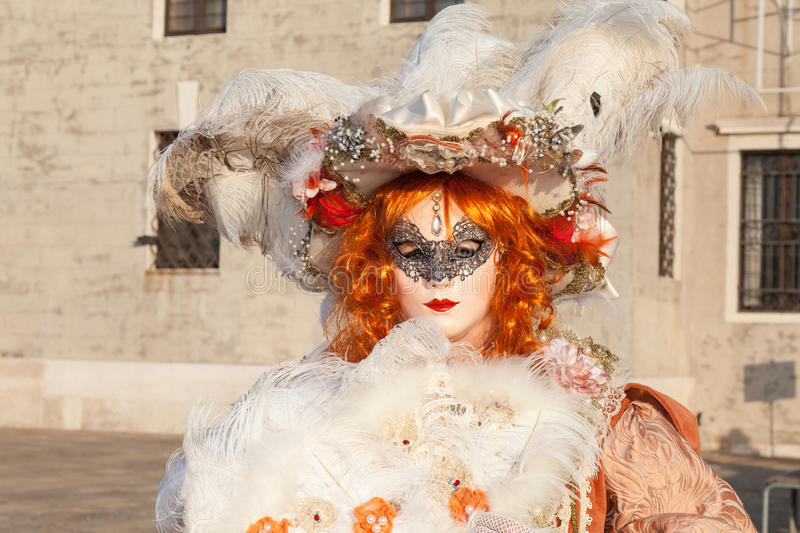 Carnival, Venice,Italy. Woman in colorful orange wig, mask. 2017 Venice Carnival, Veneto, Italy. Woman in colorful orange wig, mask and feathers in front of San royalty free stock photos