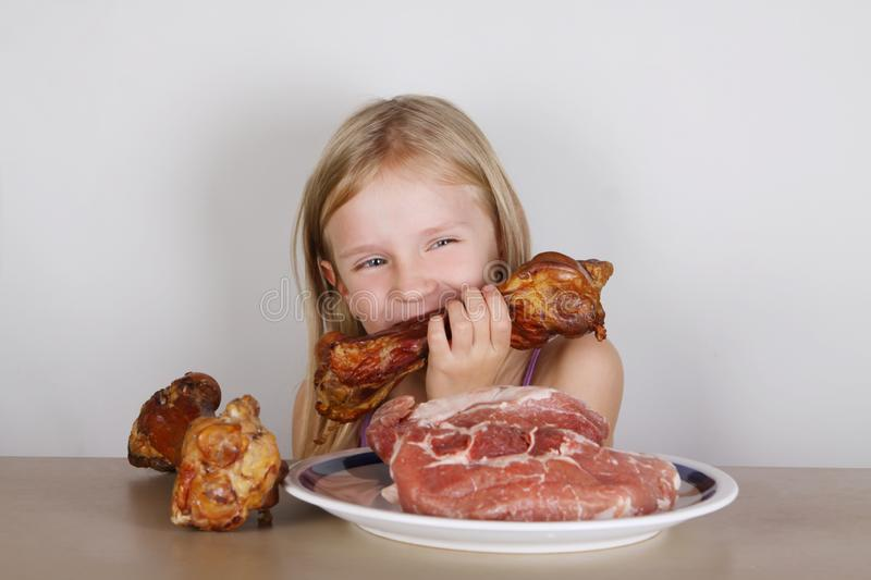 Carnivore keto diet concept - little blond girl eating raw meat. Health food stock images
