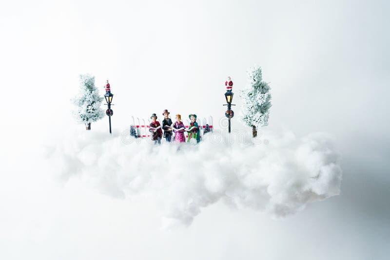 Carolers Χριστουγέννων που επιπλέουν σε ένα σύννεφο του βαμβακιού στοκ εικόνες