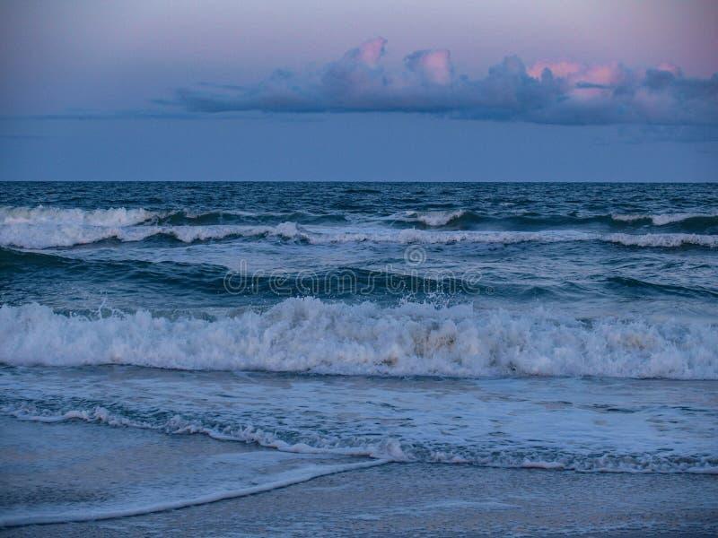 Carolina Beach Surf at Sunset. The sun setting over the surf and sand at Carolina Beach in North Carolina stock photography