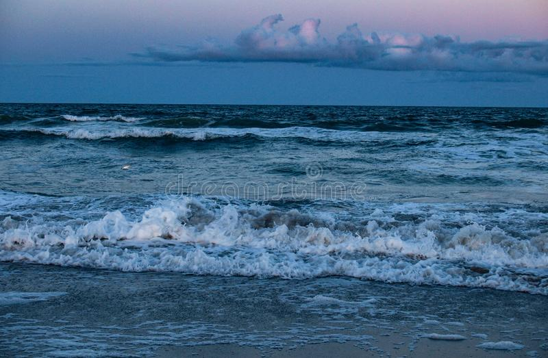 Carolina Beach Surf at Sunset. The sun setting over the surf and sand at Carolina Beach in North Carolina royalty free stock photography