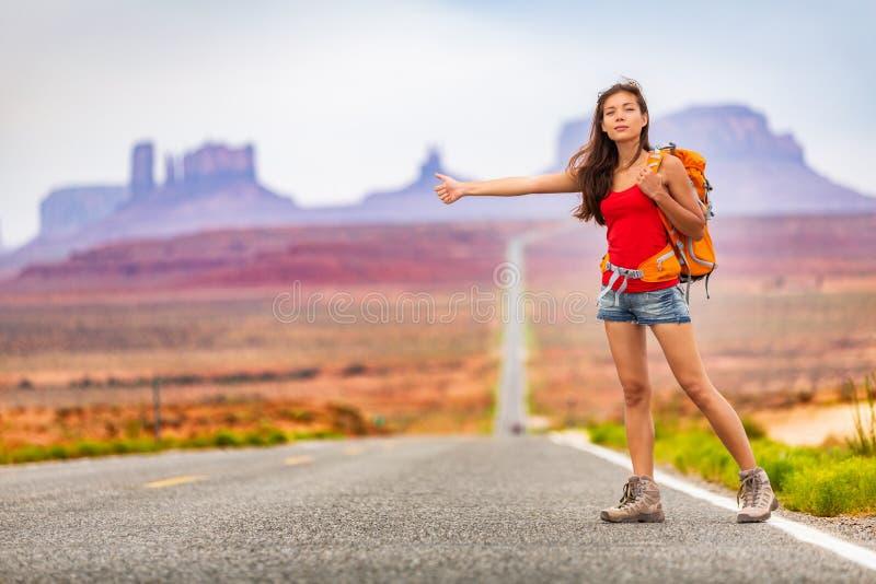 Carona backpacking da mulher do curso na viagem por estrada que engata um passeio do carro na natureza de surpresa da paisagem O  imagens de stock royalty free