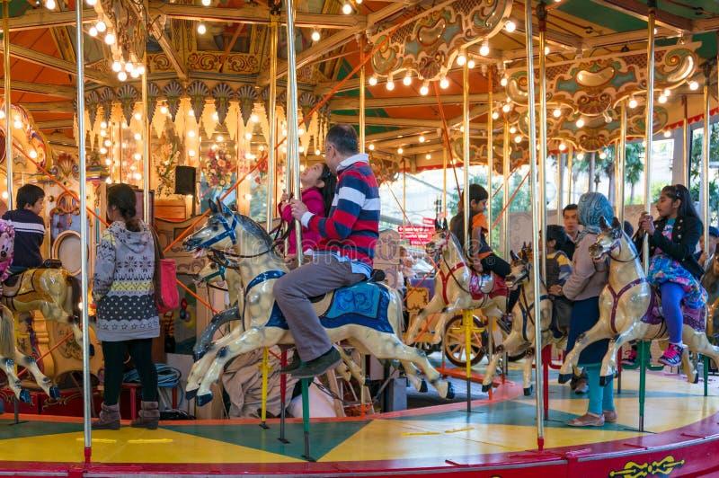 Carosello di girotondo con divertiresi degli adulti e dei bambini immagini stock
