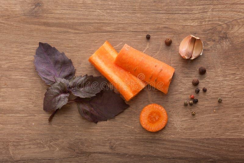 Carota, basilico porpora, spicchi d'aglio e pepe nero su w fotografia stock libera da diritti