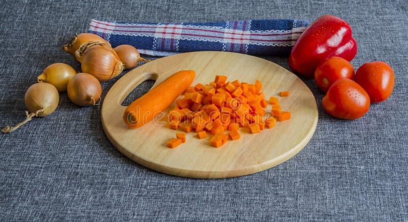 Carote affettate su un tagliere di legno Cipolle, pomodori, peperone dolce Asciugamano di cucina Su un'immagine di sfondo grigia fotografia stock libera da diritti
