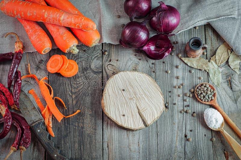 Carote e cipolle fresche su una tavola di legno grigia immagine stock
