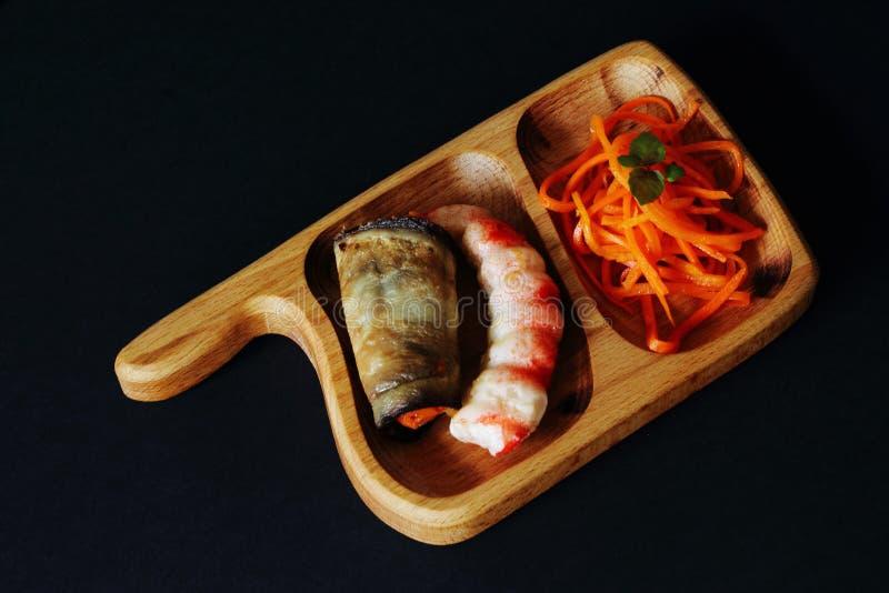 Carote marinate piccanti, vasca di melanzana arrostita farcita con le carote e gamberetto delizioso sul vassoio di legno su fondo fotografie stock