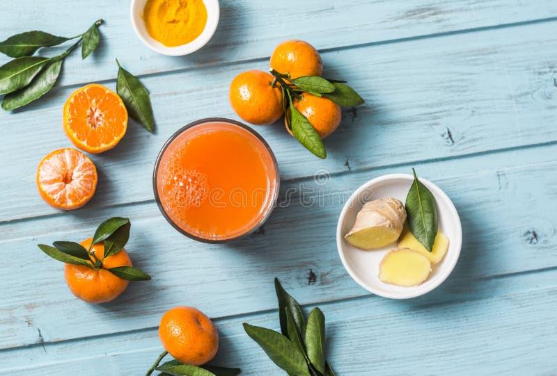Carote, zenzero, mandarini, succo fresco della disintossicazione della curcuma su fondo di legno blu, vista superiore Alimento ve fotografia stock libera da diritti