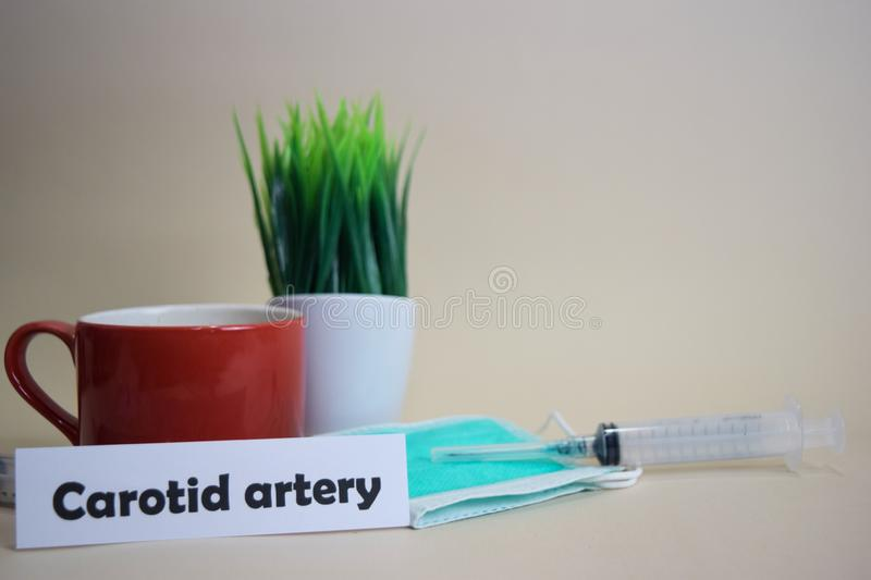 Carotid artery text, grass pot, coffee cup, syringe, and face green mask. royalty free stock photography