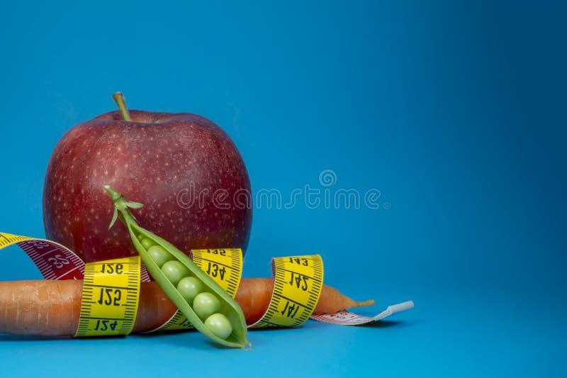 Carotte et pomme de mesure de bande sur le fond bleu photo libre de droits
