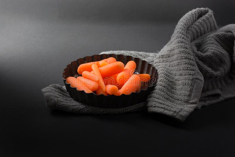 Carottes de bébé en plat de cuisson et serviette grise avec le fond foncé photo libre de droits