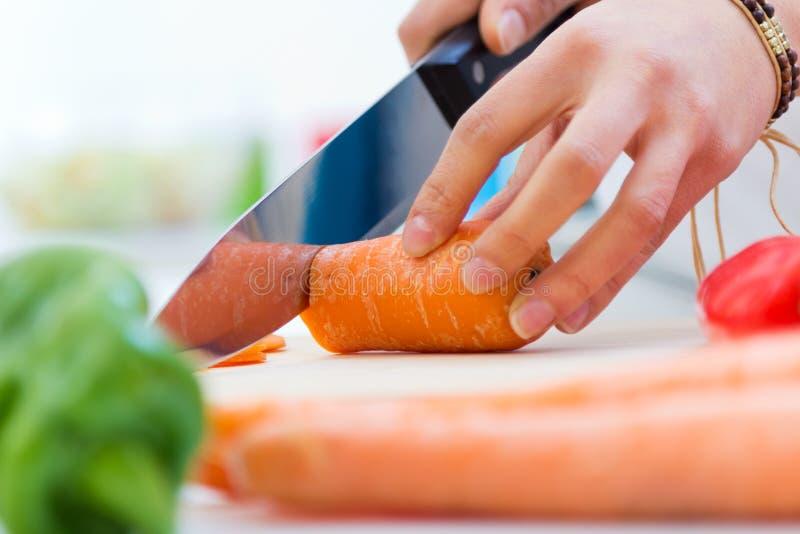 Carottes de coupe de main de femme dans la cuisine image libre de droits