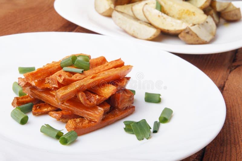 Carottes et pommes de terre cuites au four aux oignons verts d'un plat blanc image libre de droits