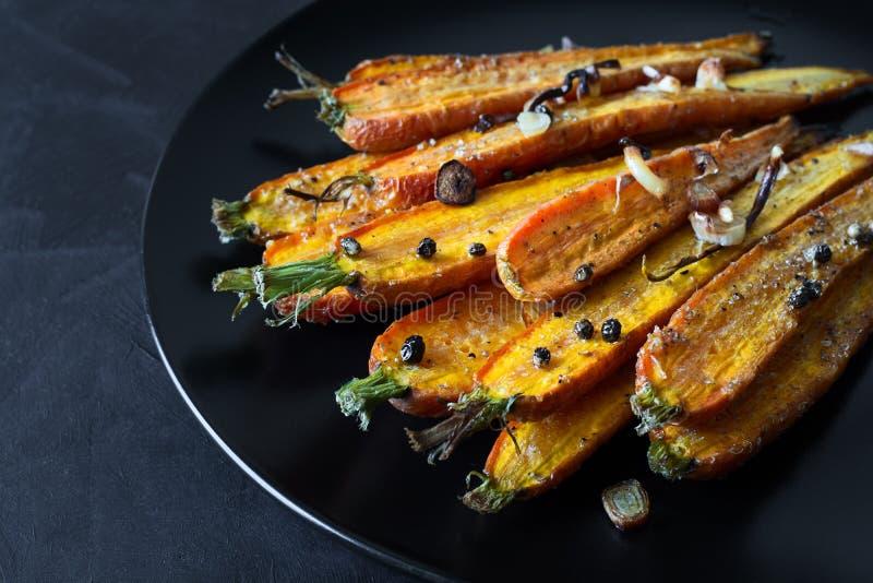 Carottes rôties de ressort de plat noir avec l'ail, les pois de poivre et la coriandre image libre de droits