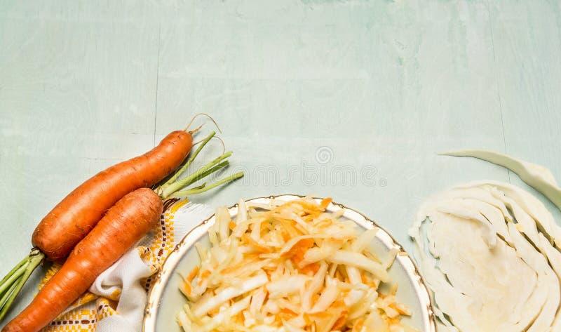 Carottes salade de chou et légumes d'ingrédients sur le fond en bois vert clair, vue supérieure image libre de droits